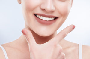 woman smiling emphasizing her hand to her smile