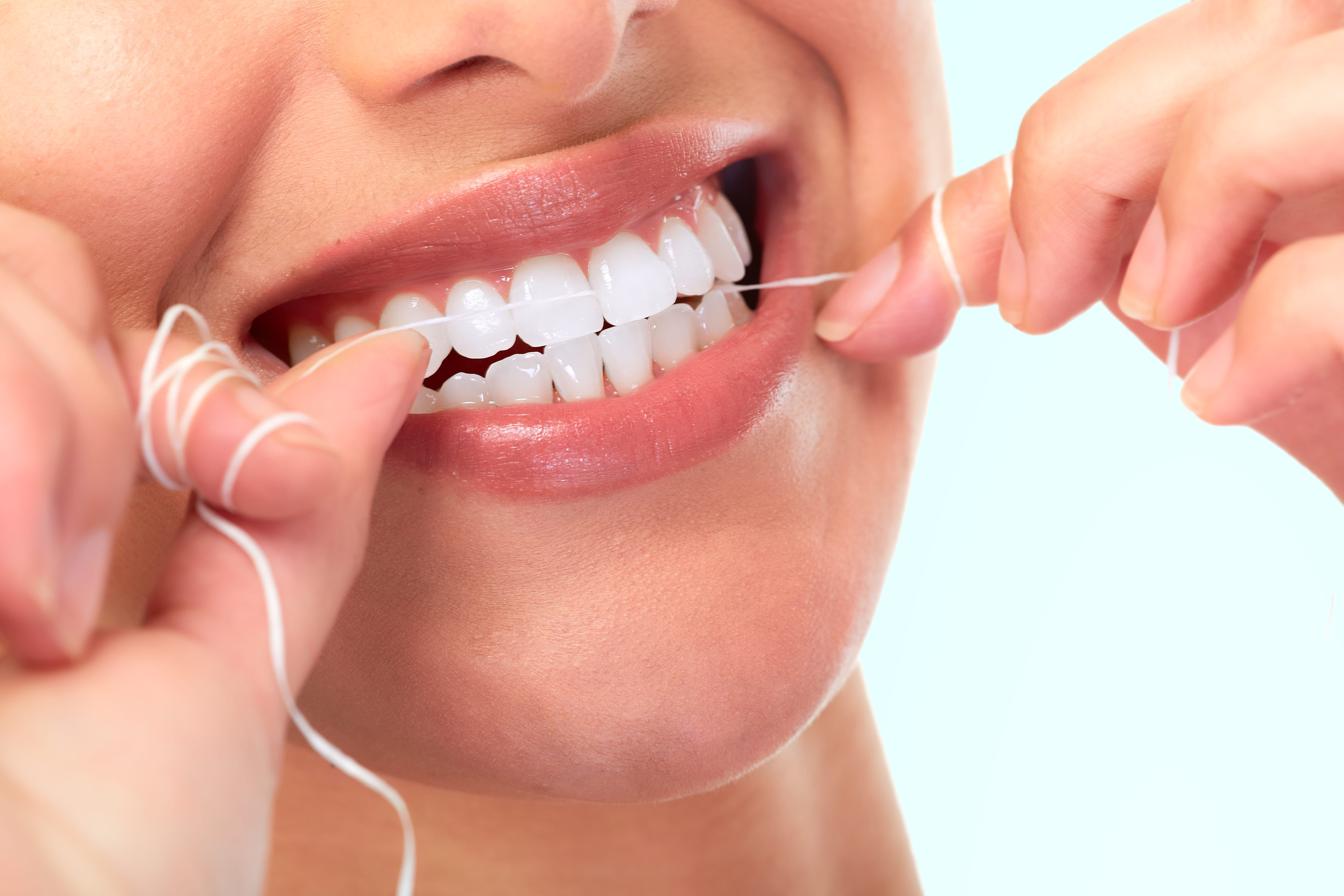Close up image of a woman flossing her teeth